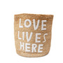 """tall standing jute basket with white embroidery that reads """"love lives here"""""""