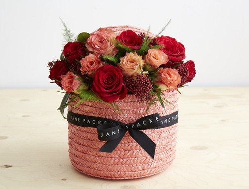 Our classic Hatbox has had a romantic, fiery update. Filled with an abundance of red sunset toned roses with a scattering of red berries and wispy flames of fern in our signature coral Hatbox.