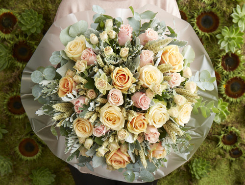 Our 'Scarecrow' bouquet is stuffed with wheat, amongst an eclectic mix of roses in soft peachy shades, with hints of blush pinks from Sweet Tacazzi roses, resting alongside Peach Avalanche and Alchemy roses with lashings of grey foliages.  Like all of our bouquets, Scarecrow is expertly made by one of our talented florists using the highest quality flowers, beautifully gift wrapped and finished with a hand written card.
