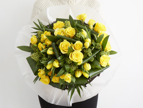 The promise of Spring, we put together this mix of Moonwalk roses, yellow spray rose, yellow tulip, green skimmia, aspirdista and chico.