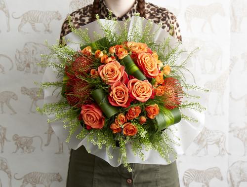 Orange Crush roses, Babe spray roses, Protea, Dracena leaves, Thlaspi Green Bell and tree fern.