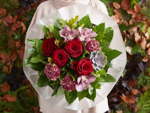 Red Explorer Roses, Viper Wine Carnations, Dark Pink Cymbidiums, Ecciveria plants.  Oak, Aralia and Salal leaves.