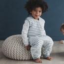 toddler-sitting-in-woolbabe-duvet-weight-sleeping-suit-tide.jpg