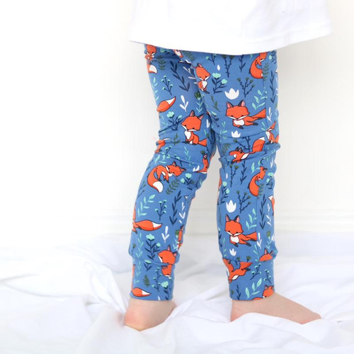 Toddler standing up, wearing unisex blue leggings with fox print