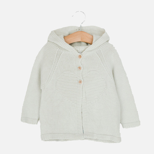 Hooded, knitted unisex jacket for toddler, cream with 3 buttons at the front, on a hanger
