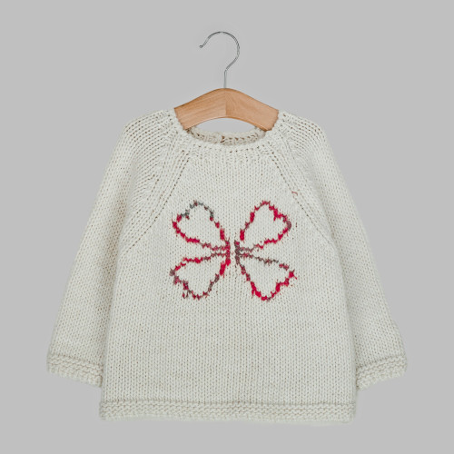 Toddler unisex cream jumper with pink and grey clover design knitted on front, on a hanger