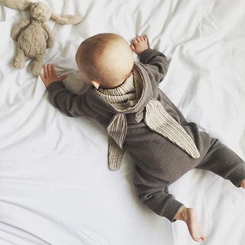 Baby lying on front, wearing a grey cotton unisex sleepsuit with bunny ears