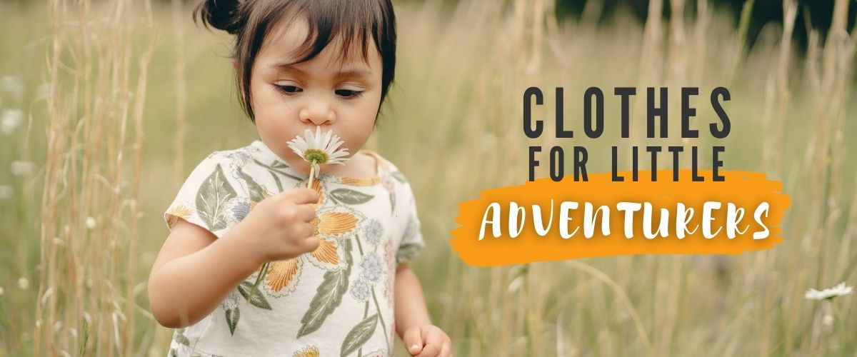 Toddler girl in colourful top exploring in a field, with text reading Clothes for Little Adventurers