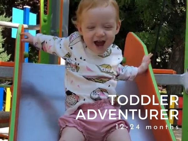 Cute image of toddler in a swing wearing a unisex fruit print top with text Toddler Adventurer 12-24 months