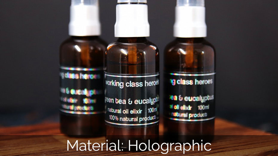 Black product holographic rectangle sticker applied to spray bottle. on a wooden block