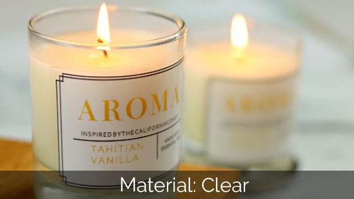 Clear sticker in a rounded corner shape applied to a vanilla candle which is lit and in front of a green plant