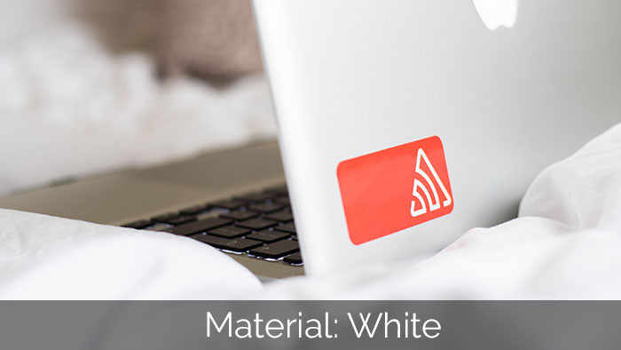Red rouned corner white vinyl sticker applied to a silver laptop on a bed