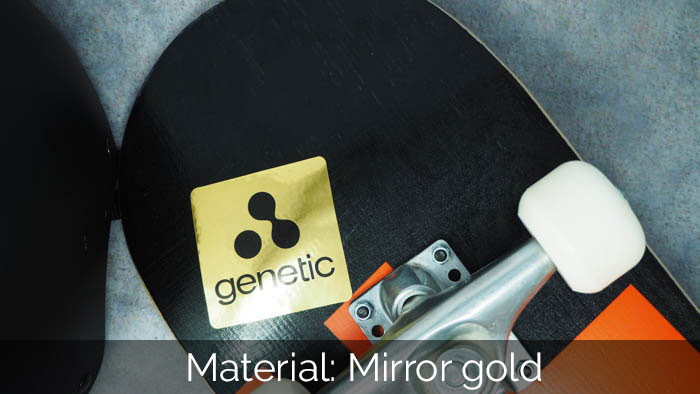 Mirror gold rounded corner sticker applied to the underside of a black and orange skateboard with white wheels