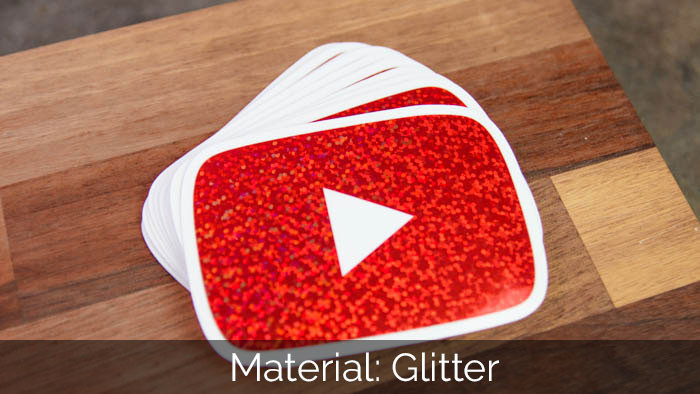 A pile of rouned corner YouTube glitter stickers on a wooden block
