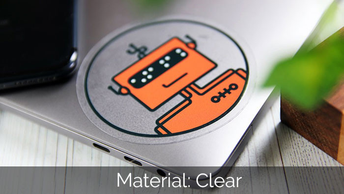 Clear robot circle sticker on a silver laptop