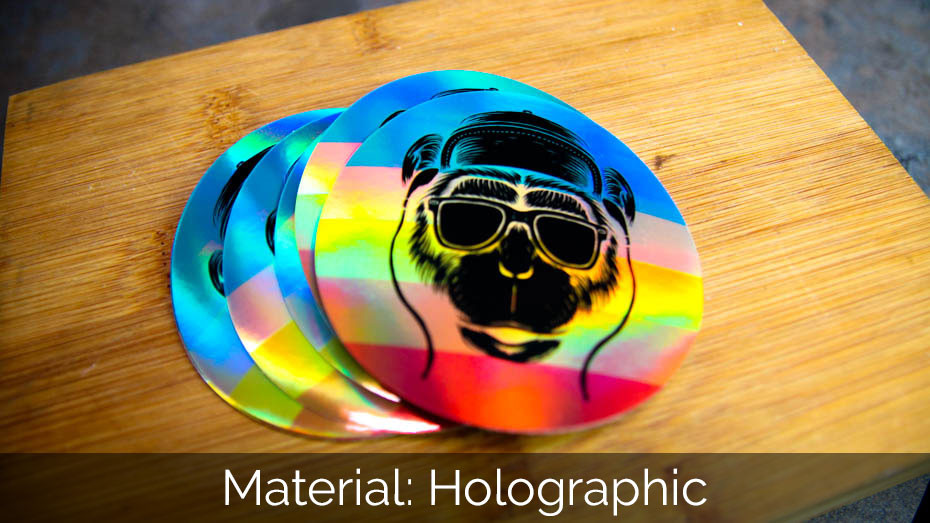 A pile of monkey circle holographic stickers on a wooden block
