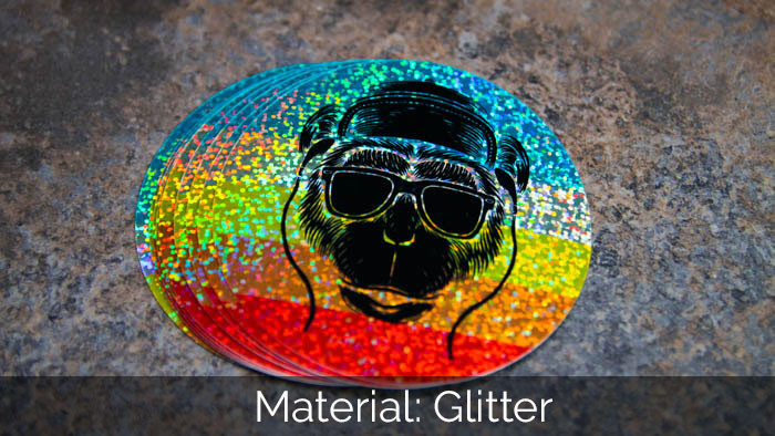 A pile of circle monkey glitter stickers on a stone tabletop