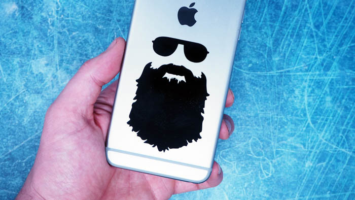 Large beard design black transfer sticker on the back of an iPhone in a persons hand with a blue background