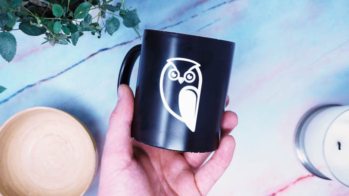 Custom made white owl transfer sticker applied to a black mug in a persons hand