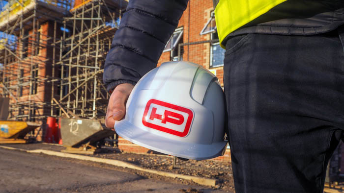 HP sticker applied to a hard hat being held in a persons hand on a construction site and scaffolding in the background
