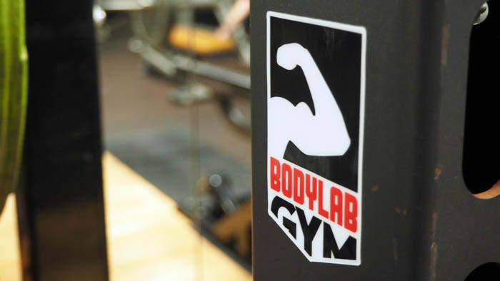 Bodylab Gym heavy duty sticker applied to a gym squat rack with a mirror in the background