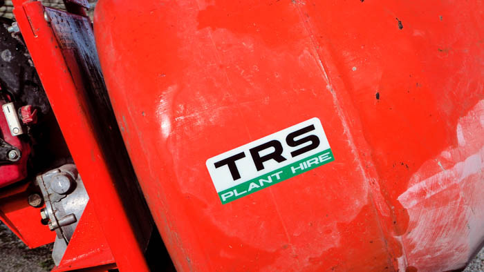 Rounded corner TRS plant hire sticker applied to the side of an orange cement mixer