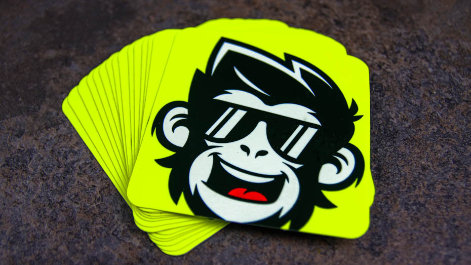 A pile of cool monkey rounded corner fluorescent yellow stickers on a dark stone slab