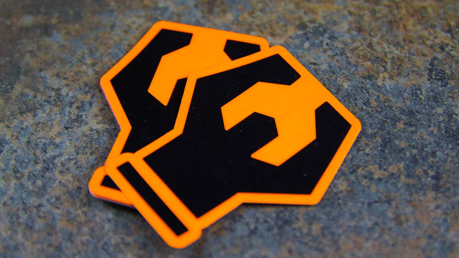A pile of wrench die cut fluorescent orange stickers on a dark background