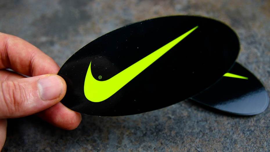A pile of Nike oval fluorescent yellow stickers on a stone slab with 1sticker in a persons hand.