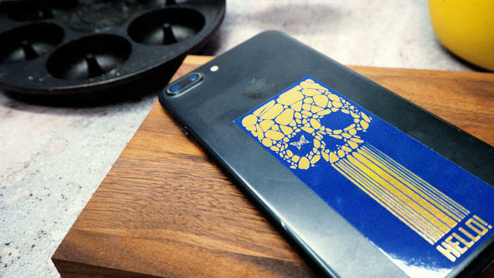 Black iPhone with a sticker applied on a wooden chopping board and a pancake frying pan in the background
