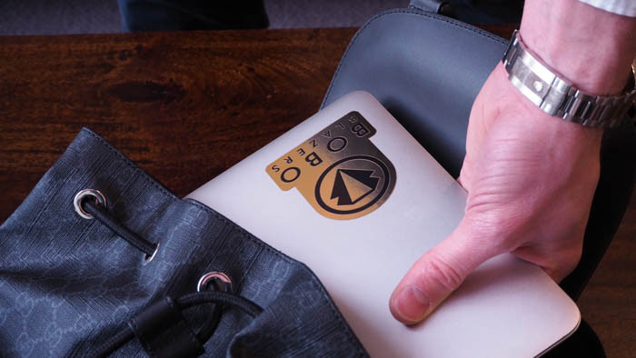 Gold sticker applied to a silver laptop being put into a Gucci backpack by a person wearing a silver Rolex watch