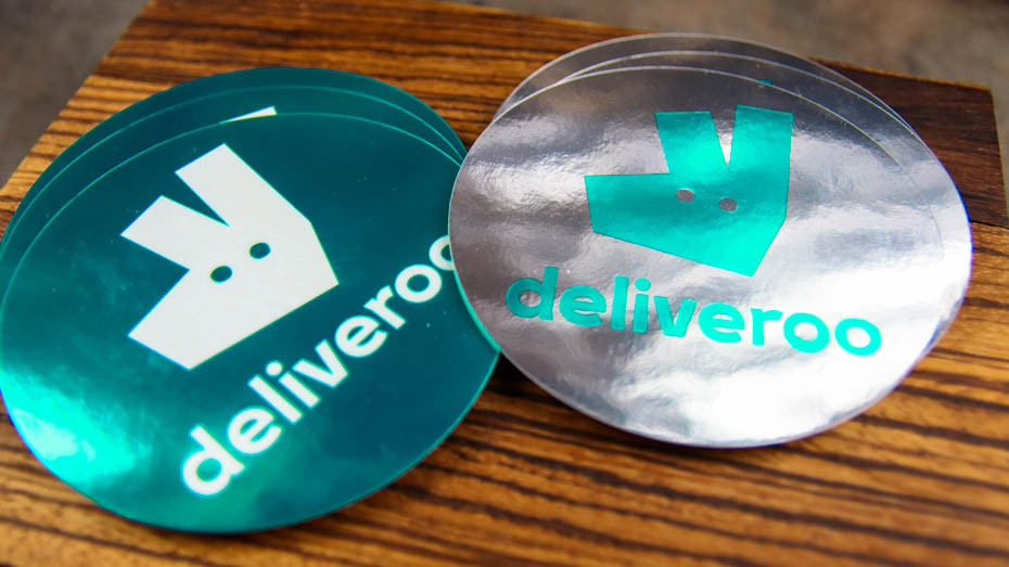 A pile of Deliveroo circle mirror silver stickers on a wooden work surface
