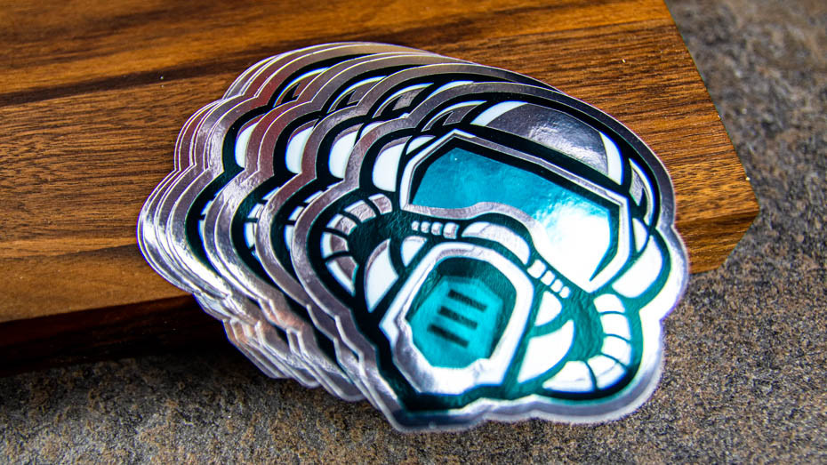A pile of masked figher die cut mirror silver stickers on a wooden block