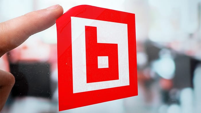 Red and white square front adhesive sticker with a finger starting to peel it away