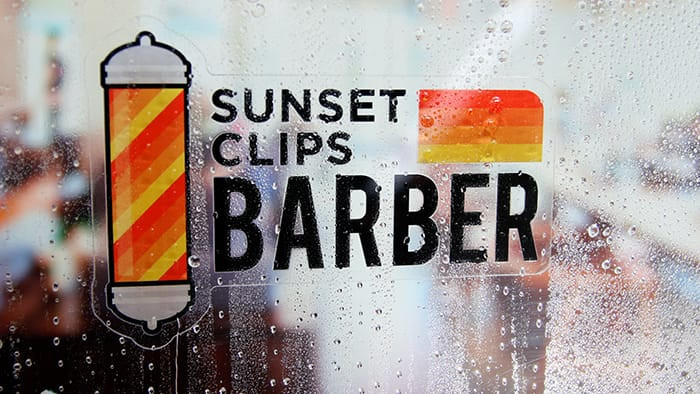 Sunset clips barber die cut front adhesive sticker on the inside of a window in the rain