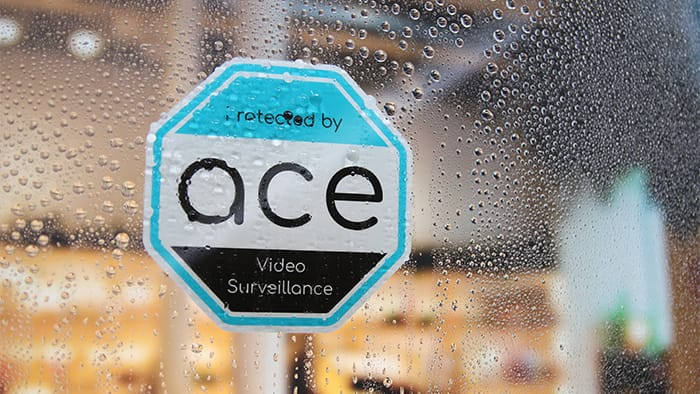 ACE video surveillance die cut front adhesive sticker on the inside of a window in the rain