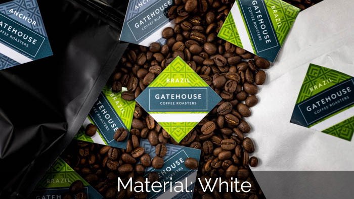 Square white vinyl coffee stickers in a pile of coffee beans