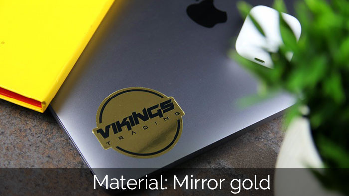 Viking mirror gold die cut sticker applied to a laptop with a yellow notepad and plant