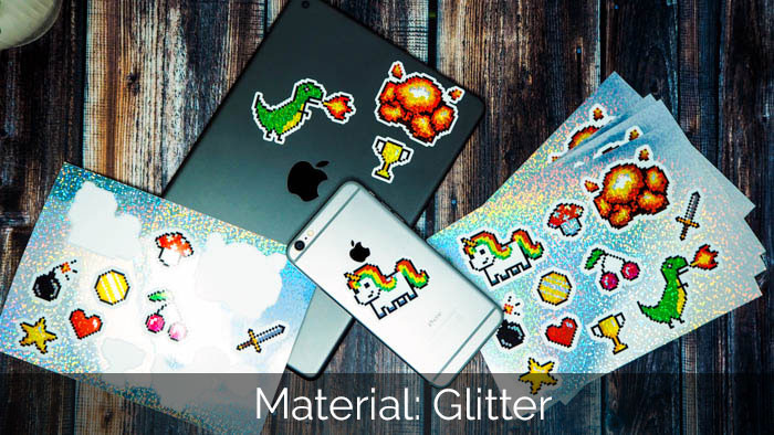 Glitter sticker sheets with awesome full colour designs including white ink, lying on a dark wood table next to an iPhone and iPad