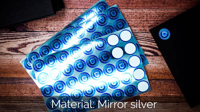 Mirror silver sticker sheets lying on a wooden table with one applied to a black notebook