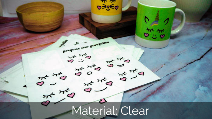 Clear sticker sheets with cute unicorn design and smiley faces with some stickers applied to colurful mugs