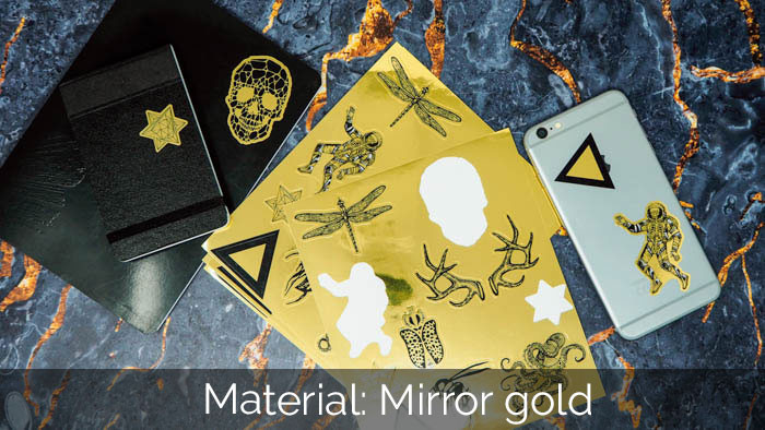 Mirror gold sticker sheets next to an phone and black book on a stone surface