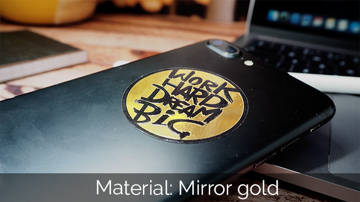 Work hard dream big gold circular sticker on the back of a mobile phone lying on a laptop