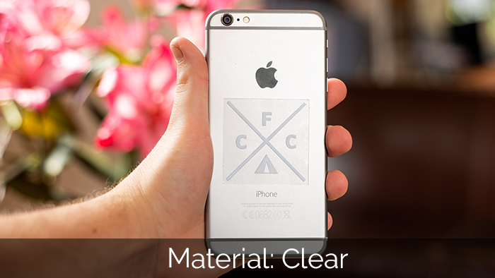 Clear square sticker applied to a silver phone in a hand