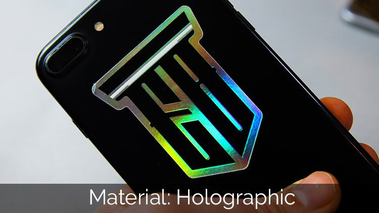 Die cut holographic EB logo sticker on the back of a black phone