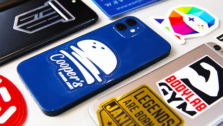 iPhones with lots of different stickers on a grey background.