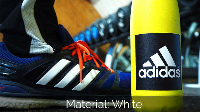 Square white adidas sticker on a yellow waterbottle in the gym