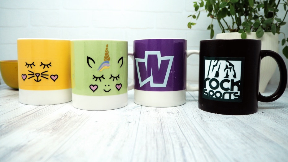 4 mugs with square mug stickers applied sitting on a wooden table with a plant in the background