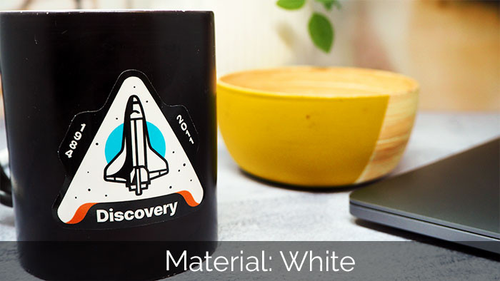 Space rocket sticker in a triangle shape applied to the side of a black mug with a yellow bowl in the background