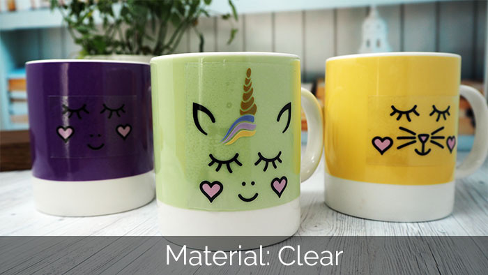 2 colourful mugs with a unicorn and cat face sticker applied to them on a wooden worksurface